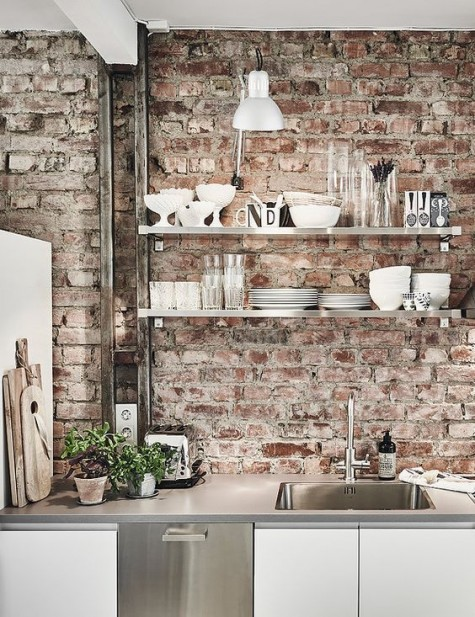 a shabby red brick wall and shiny metal touches add interest to this modern Nordic kitchen