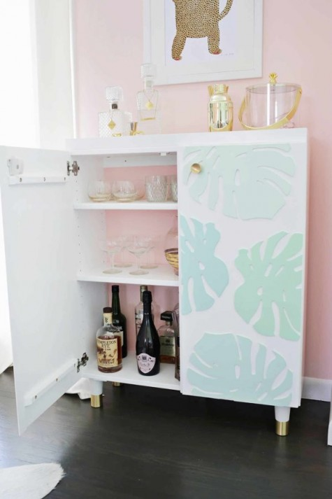 an IKEA Ivar cabinet turned into a stylish kid proof home bar with 3D tropical leaves and pink backing inside
