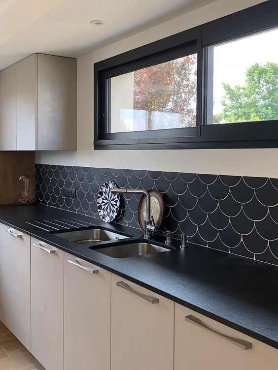 a monochromatic kitchen with black countertops, black frames and a black fishscale tile backsplash to make the space cohesive