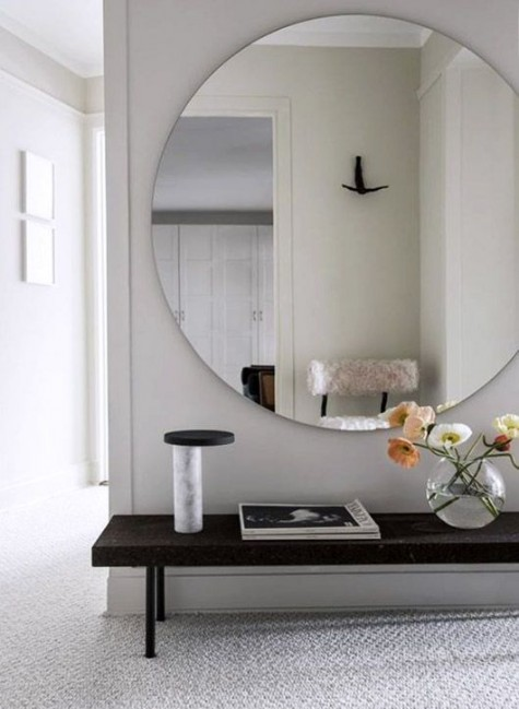 a small yet trendy entryway with an oversized mirror and a bench - who needs more