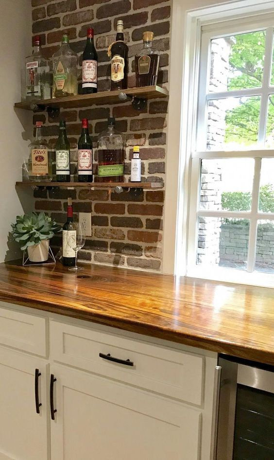 a white farmhouse kitchen with a rich stained butcher block and a red brick wall for more eye-catchiness