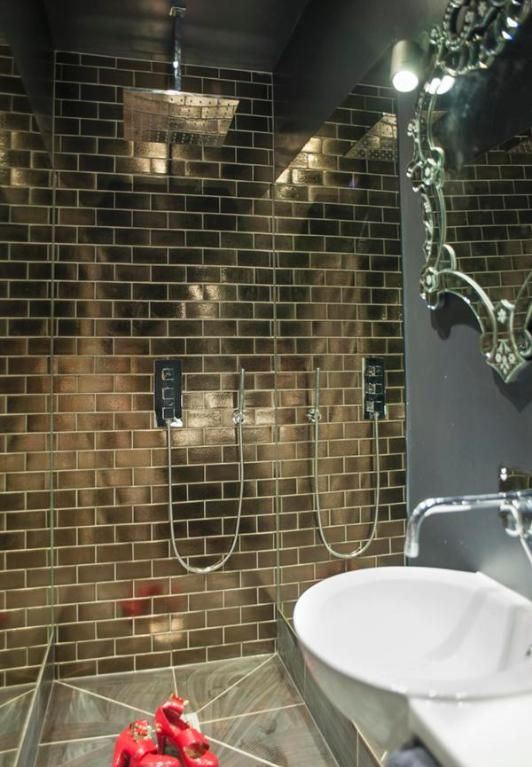 shiny copper tiles mark the shower space the best way possible and it stands out in a grey space