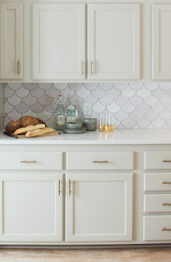 a chic neutral kitchen with a marble fishscale tile backsplash that make it interesting and catchy at once