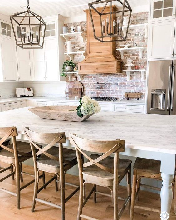 a neutral farmhouse kitchen with white cabinets, a red brick backsplash and some metal lanterns over the island