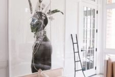 23 a small sunroom with an oversized artwork that takes over the whole space creating a mood