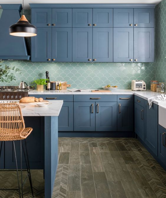 a beautiful blue kitchen with white stone countertops and a green fishscale tile backsplash
