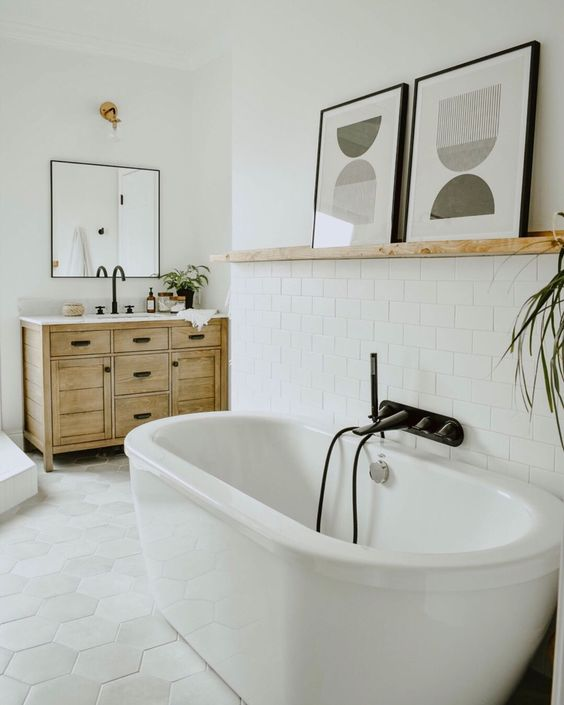 a neutral bathroom with an oval tub, a shelf with a duo of abstract artworks for a bolder and catchier look