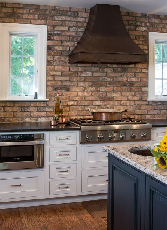 a shabby red birck wall and a darkened metal hood add interest to the space and stone countertops match