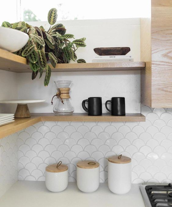 a neutral kitchen with wooden shelves and a white fishscale tile backsplash for a fresh and airy feel