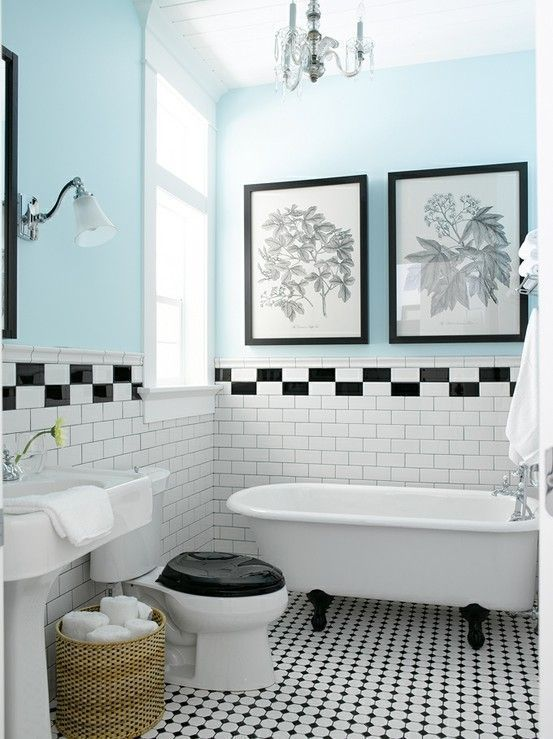 a pretty small bathroom with black and white botanical artworks over the bathtub