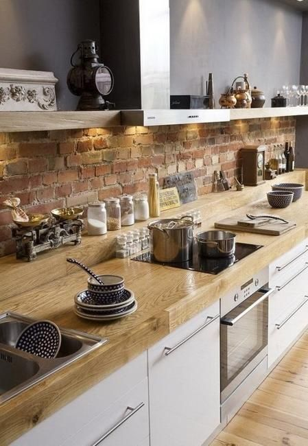 a contemporary kitchen with white cabinets, light-colroed butcherblock countertops and a red brick backsplash