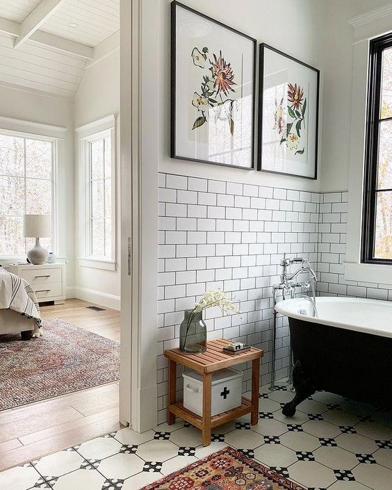 a monochromatic bathroom with avintage touch and bright botanica artworks reminding of vintage posters