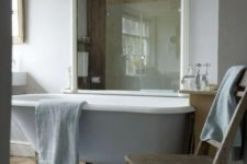 26 a relaxed vintage bathroom with a lilac clawfoot tub and a large mirror in a white frame