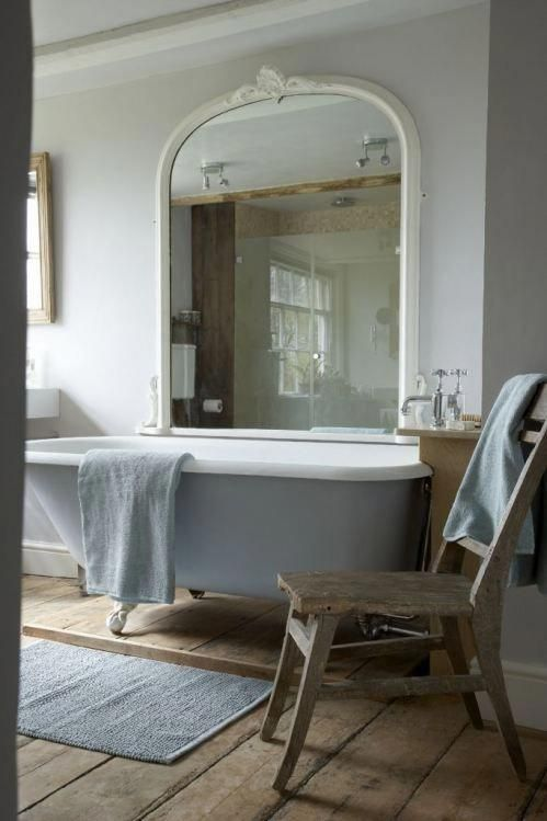 a relaxed vintage bathroom with a lilac clawfoot tub and a large mirror in a white frame
