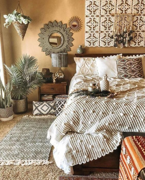 a Moroccan boho bedroom with a cutout screen, printed textural pillows, layered rugs, potted plants and unique mirrors
