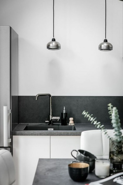 a Scandinavian space with a concrete countertop and backsplash that spruce up usual white cabinets