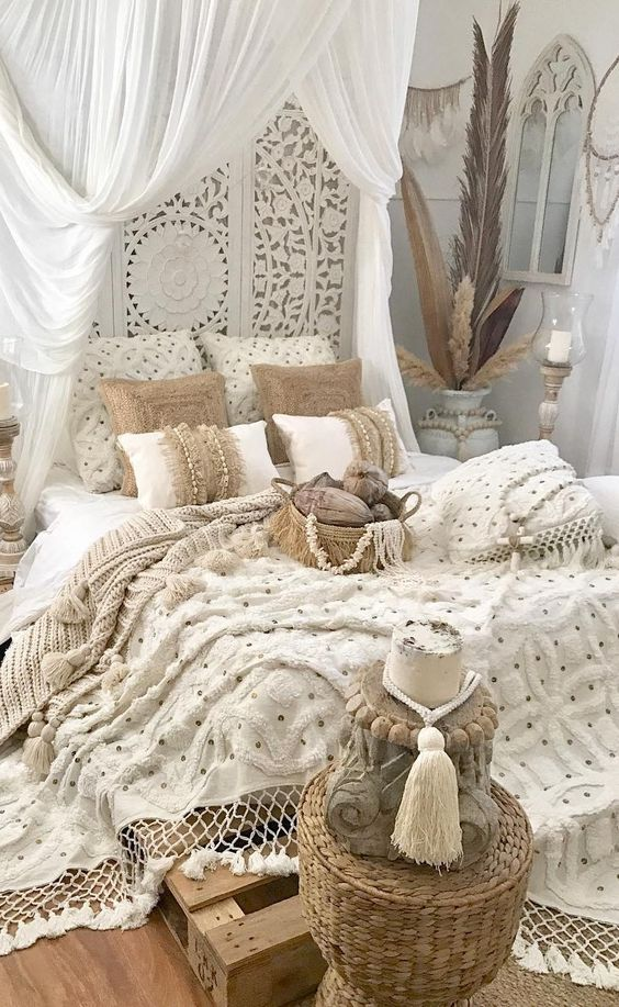 a boho Moroccan bedroom with a laser cut screen, layered fringe and tassel bedding and blankes plus beads and feathers