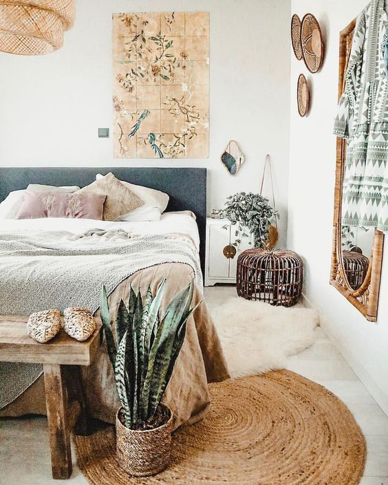 a boho bedroom with an upholstered bed, layered rugs, potted plants, a wicker lamp and decorative plates on the wall