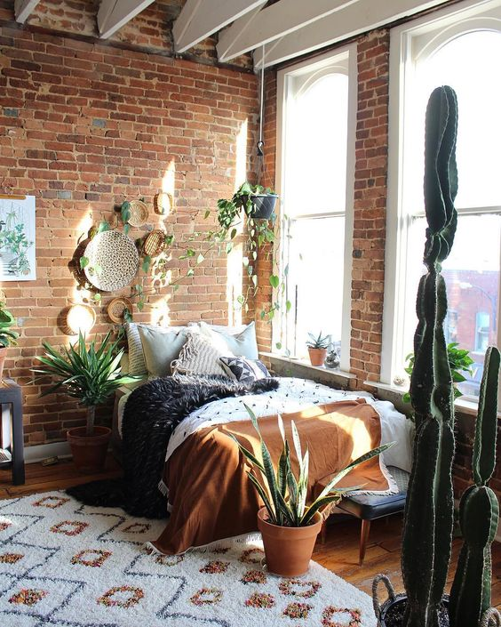 a boho bedroom with brick walls, potted succulents and cacti, colorful blankets and decorative plates on the wall