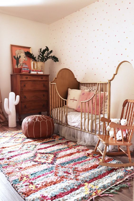 a boho bursery with a rich stained dresser, a vintage crib, a leather ottoman, a colorful rug and a polka dot wall