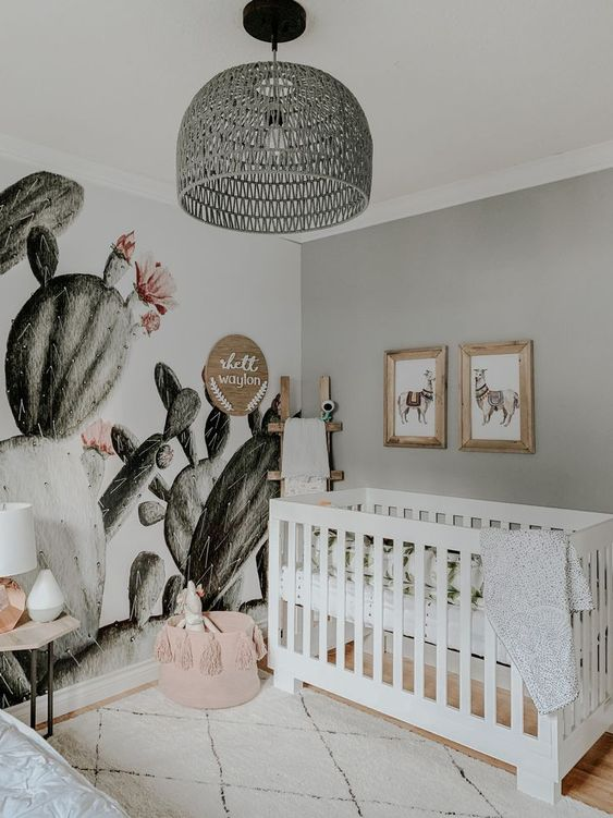 a boho desert nursery with a cactus wall, a pink tassel basket, a grey rattan lamp and llama artworks over the crib