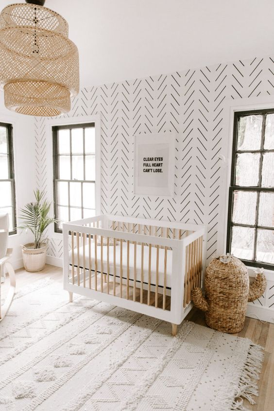 a boho desert nursery with a printed wall, a cactus wicker basket, a wicker lamp, a Moroccan blanket rug and potted greenery