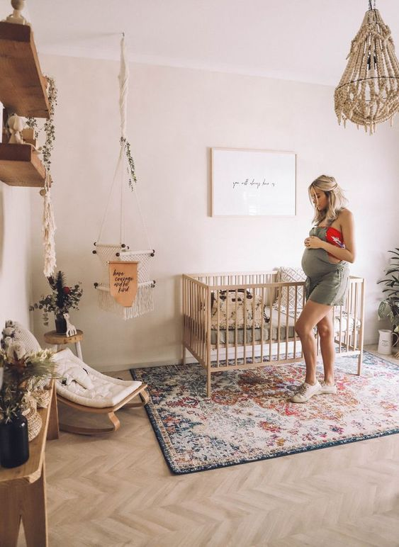 a boho nursery with a colorful printed rug, a beaded chandelier, natural wooden furniture and lots of greenery