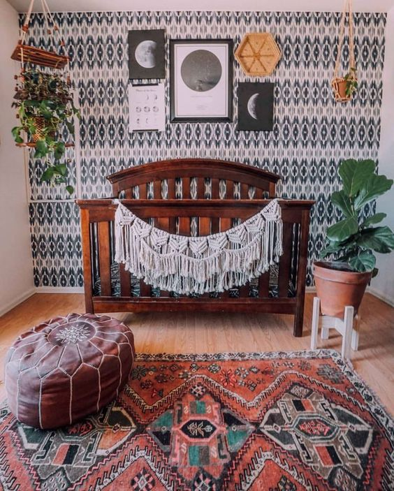 a boho nursery with a rich stained bed, a macrame garland, a gallery wall, lots of plants and a bright rug and a leather ottoman