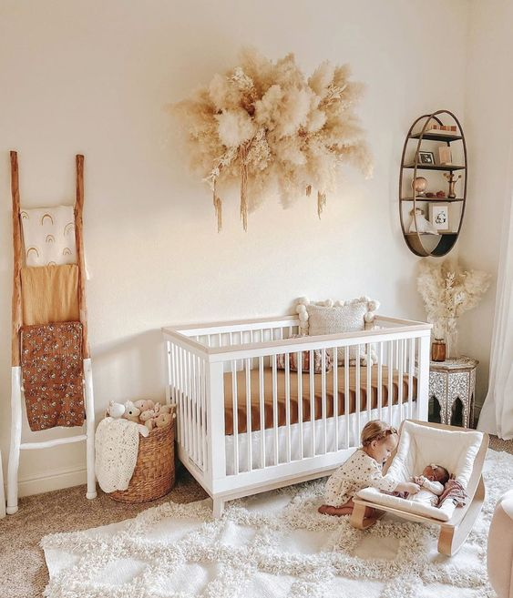 a boho nursery with a white crib, a ladder with colorful textiles, a Moroccan table and a pampas grass mobile