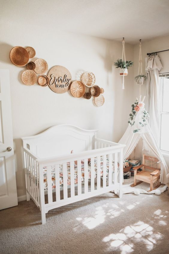 a boho nursery with a white crib, baskets on the wall, a teee for reading and some suspended plants