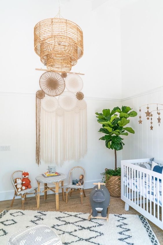 a boho nursery with a wicker lamp, dream catchers, layered rugs,, a potted tree and printed textiles all over