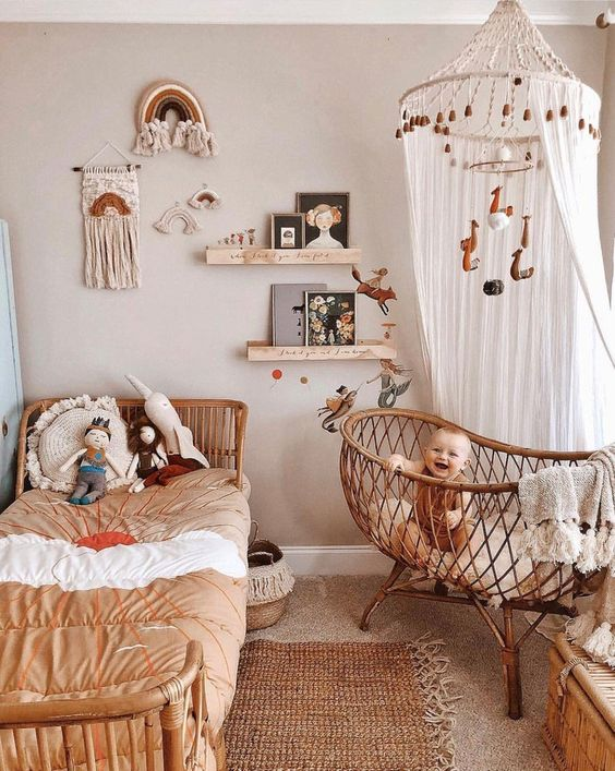 a boho nursery with wicker furniture, a large canopy with pompoms and a mobile, a gallery wall with macrame