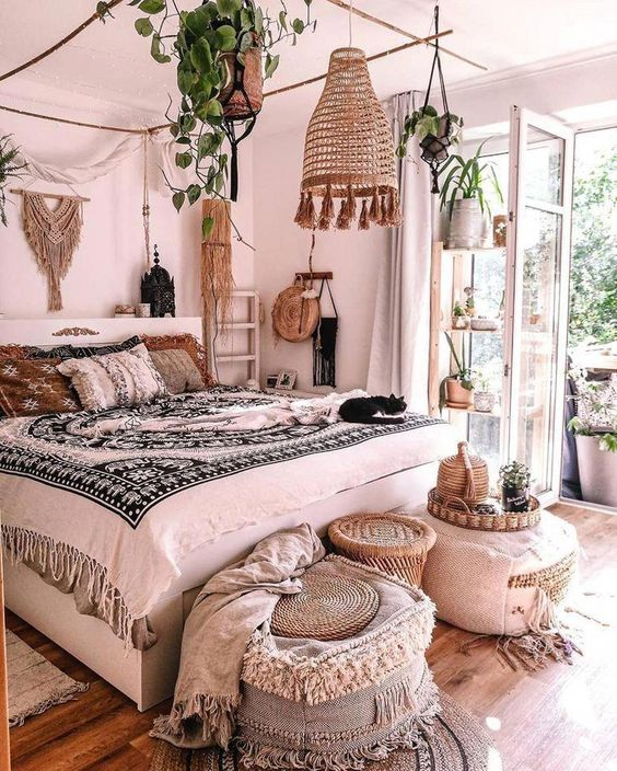 a boho space with lots of printed pillows and blankets, ottomans with tassels and fringe, potted plants hanging over the bed