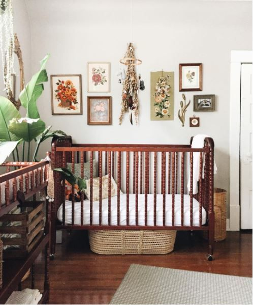 a bold boho nursery with a gallery wall, dark stained furniture, layered rugs and tropical plants in pots