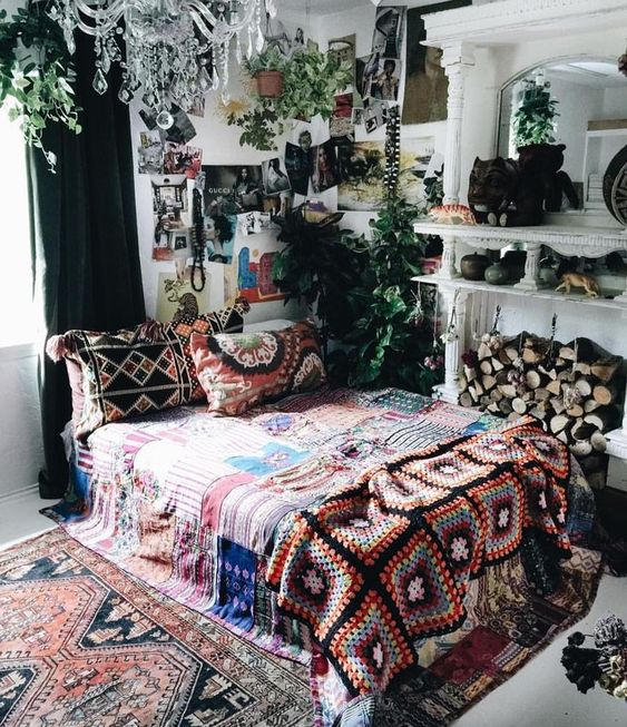 a bold boho room with much greenery hanging in pots, lots of prints and a gallery wall plus a crystal chandelier