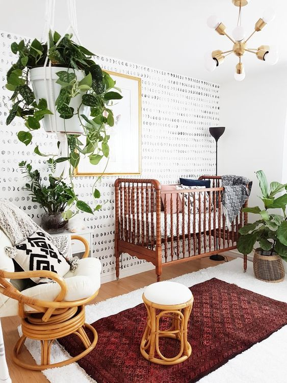a bold mid century and boho nursery with lots of potted greenery, a vintage bed, rattan furniture, gold touches and layered rugs