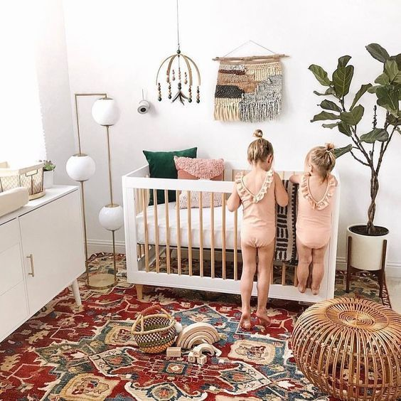 a bright boho nursery with a colorful rug, a potted plant, macrame and a beaded chandelier and neutral furniture