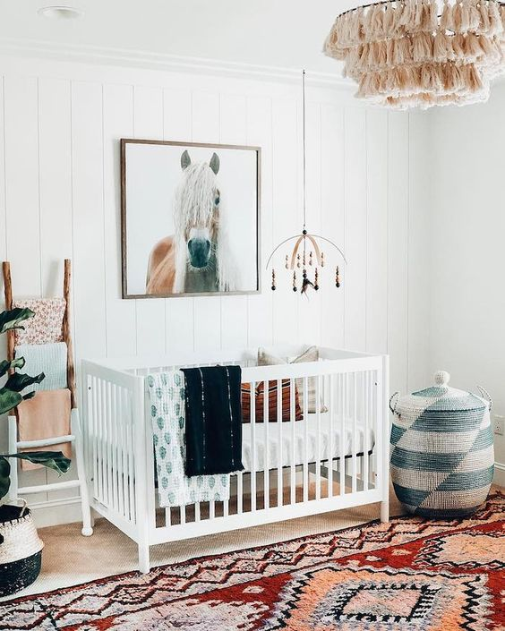 a bright boho nursery with a colorful rug, a printed basket with a lid, a macrame chandelier, colorful textiles and a horse artwork