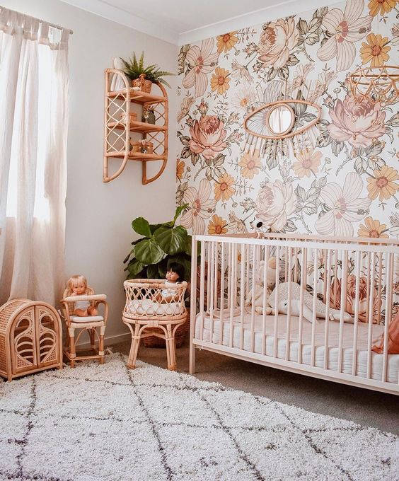 a bright boho nursery with a floral statement wall, wicker furniture and toys, a crib and potted plants plus a printed rug