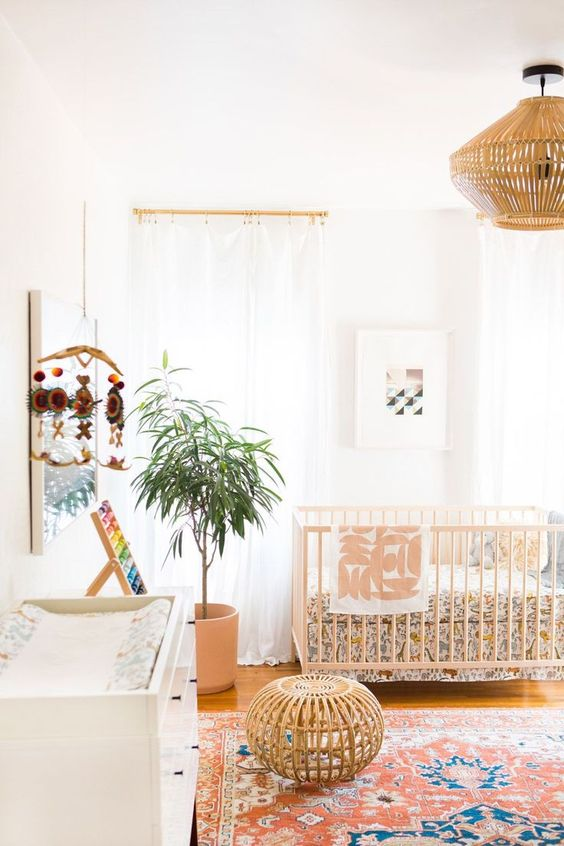 a bright boho space with colorful printed textiles, a rattan orroman and lamp, potted greenery and a colorful mobile