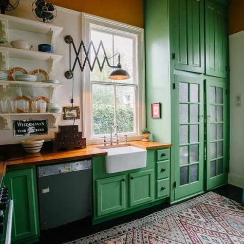 a bright green kitchen with butcher block countertops that contrast the cabinets and calm them down