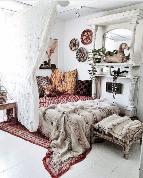 a chic boho bedroom in white, with a large mirror, bright printed pillows and blankets, a lace curtain and decorative plates