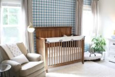 a chic farmhouse nursery with a blue and white plaid wall, a vintage wooden crib, cozy textiles and a potted plant