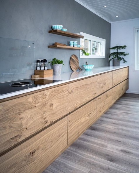 a contemporary kitchen with wooden cabients and a concrete backsplash plus a glass cover over it