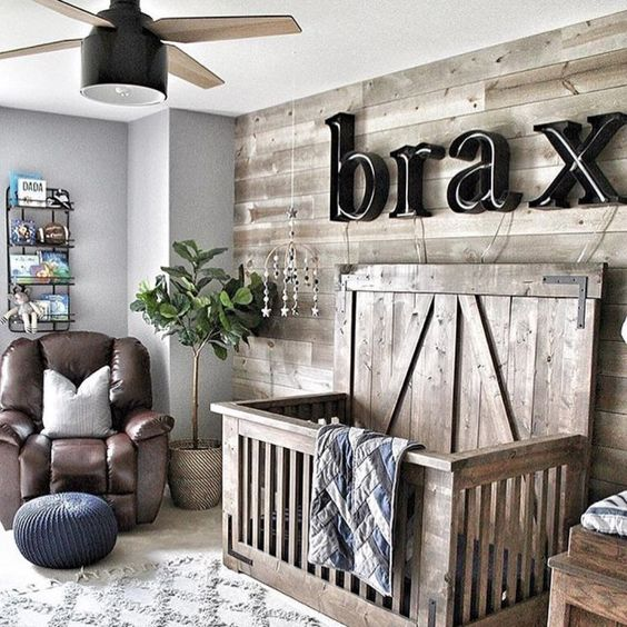a cozy rustic nursery done with plenty of wood, a leather chair, potted greenery and giant letters on the wall
