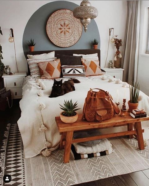 a cute boho bedroom with printed pillows, potted greenery, a Moroccan lamp and a wooden artwork plus pompoms