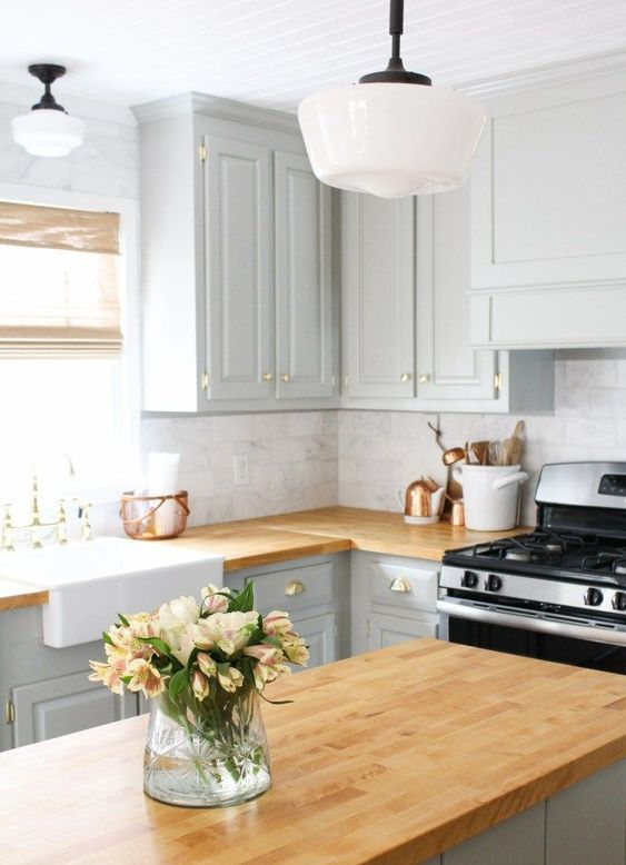a dove grey kitchen with warm light-colored butcher block and a wicker shade for a warm touch