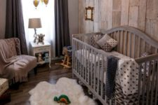 a farmhouse nursery with a reclaimed wooden wall, dark textiles, a grey crib, some gold touches here and there