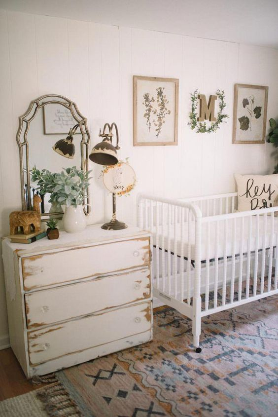 a farmhouse nursery with a white crib a shabby chic dresser, a vintage mirror and a lamp plus botanical touches