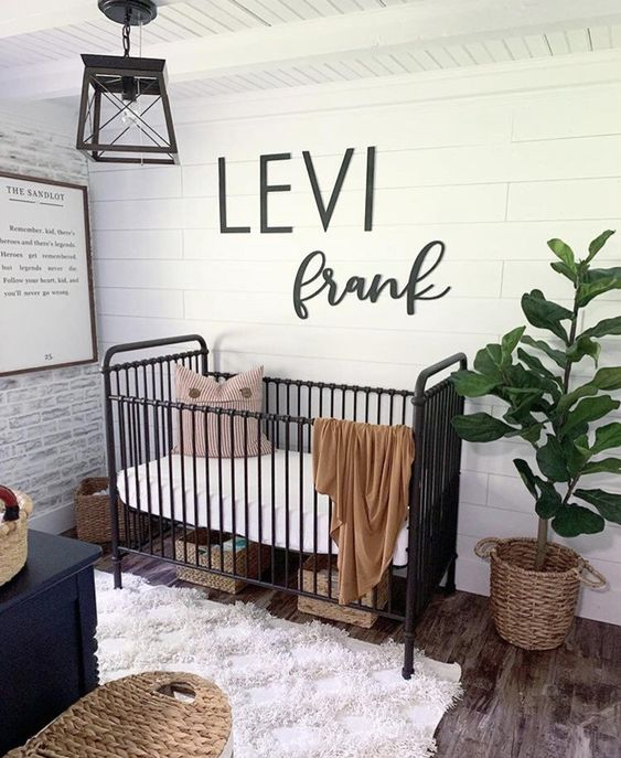 a farmhouse nursery with a white plank wall, a brick one, a black metal crib and lamps, wicker and woven items